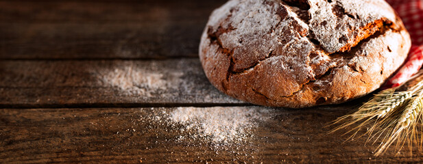 Fresh baked bread on rustic wood Fresh crispy bread and flour on rustic wood. Horizontal background for a bakery concept with space for text.