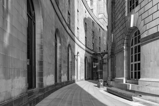 Black and white photo of the curve of library walk in Manchester with the late evening sunlight casting into the shot.