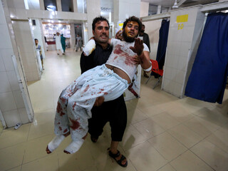 A man carries an injured person in a hospital after blasts, in Jalalabad