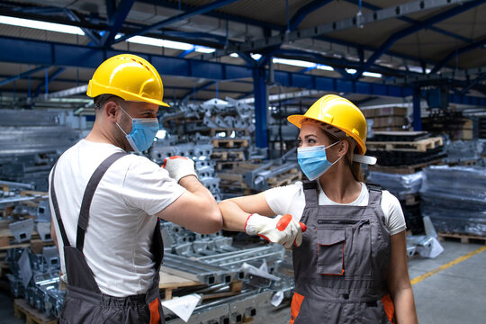 People working at factory touching with elbows and greeting due to corona virus and infection. Employees in factory wearing protection mask.