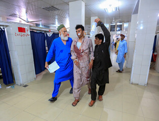 Men help an injured person in a hospital after blasts, in Jalalabad