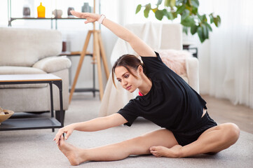 Yoga workout at home. Attractive young woman doing stretching in living room.