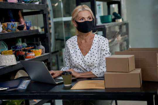 Small business after lockdown quarantine. Female business owner or business woman wearing protective face mask working on laptop in her art studio or craft pottery shop