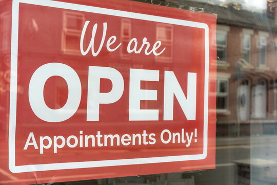 outdoor sign showing pandemic services during virus. Text on vintage red sign 'We are OPEN Appointments Only!' A business sign stating OPEN handing door at the hairdresser or beautician. Hair dresser.