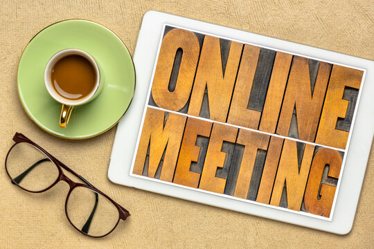 online meeting word abstract in vintage letterpress wood type on a digital tablet, networking, telecommunication and work from home concept