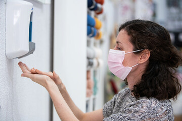 Woman disinfecting her hands on a retail shop due to pandemic disease covid 19.