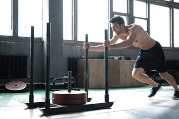 Fit male athlete doing exercises working out in the gym