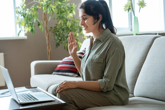 Happy indian woman online teacher female tutor wear headset looking at laptop making business conference video call on computer virtual meeting for distance job interview sit on couch at home office.