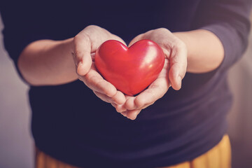 Woman holding red heart, health insurance, donation, happy charity volunteer concept, world mental health day, world heart day