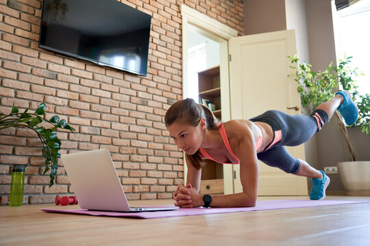Fit sporty young woman doing plank online workout exercise at home. Active healthy girl enjoy sport pilates yoga fitness training on laptop computer stretching on yoga mat watching video class.