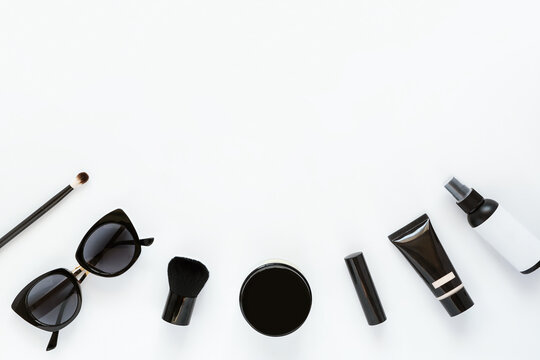 Makeup cosmetic beauty products black flat lay composition on white background, top view.