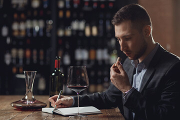 Sommeliers male tasting red wine and making notes aroma degustation card