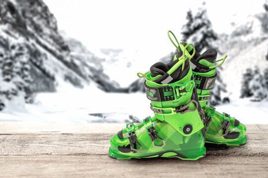 ski boots on a wooden table against the background of mountains. bright green sports ski boots