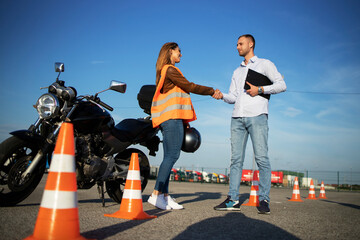 Motorcycle driving school. Instructor and student handshake before start of the classes. Safe ride...