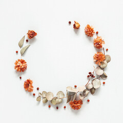 Autumn composition. Wreath made of dried flowers, eucalyptus leaves, berries on gray background. Autumn, fall, thanksgiving day concept. Flat lay, top view