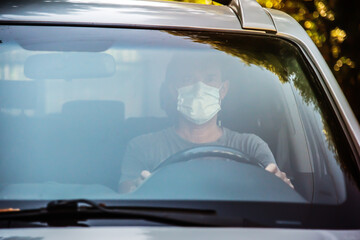 Man with virus protection mask driving a car