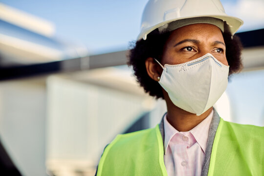 Female African American civil engineer with protective face mask at construction site.