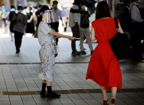 A saleswoman wearing a face shield distributes leaflets on the street amid the coronavirus disease (COVID-19) pandemic in Tokyo