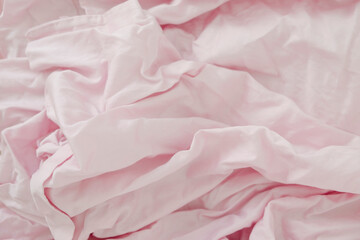 Crumpled pastel pink bed linen for light background.