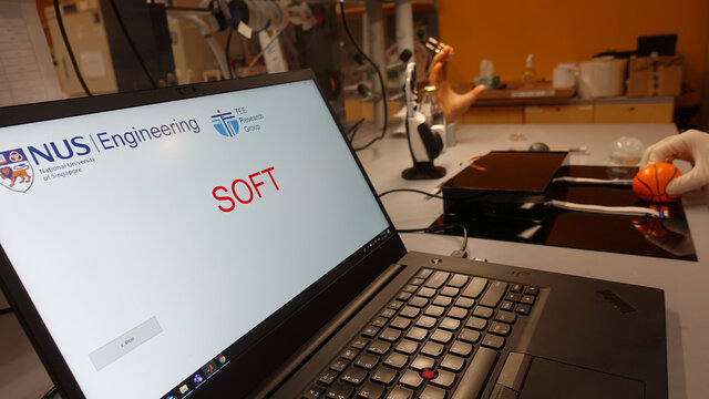 Dr. Benjamin Tee demonstrates how his device can detect the texture of a squishy stress ball at a NUS lab in Singapore