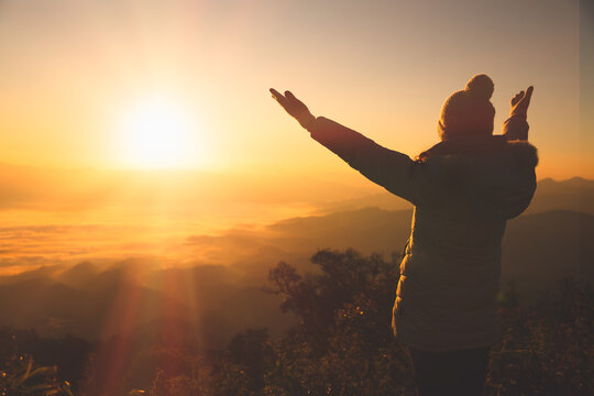 Copy space of silhouette woman raise hand up on top of mountain and sunset  background. Freedom feel good and travel adventure holiday concept. Religious beliefs