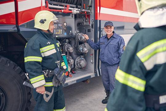 Team building meeting of firefighters near the modern fire truck
