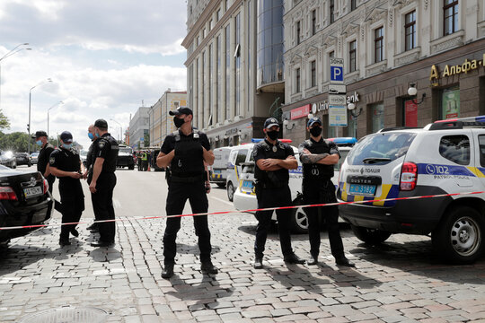 Police officers stand guard outside a building where an unidentified man reportedly threatens to blow up a bomb in a bank branch, in Kyiv