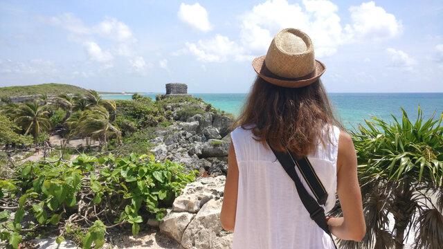 Woman tourist staring at Mayan Ruins in Tulum, Riviera Maya, Mexico