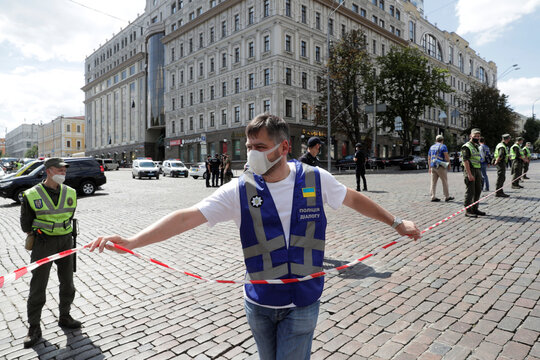 Law enforcement officers are seen outside a building where an unidentified man reportedly threatens to blow up a bomb in a bank branch, in Kyiv