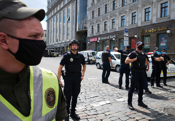 Law enforcement officers stand guard outside a building where an unidentified man reportedly threatens to blow up a bomb in a bank branch, in Kyiv