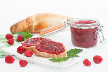 Raspberry jam with fresh raspberries and bread slices on white background. Homemade marmalade, perfect for light, sweet breakfast.
