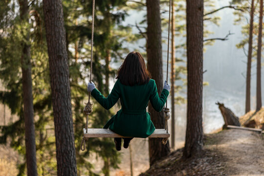 Rear View Of Woman Sitting On Swing In Forest