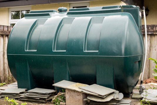 A green plastic fuel oil tank in a rural garden in Cornwall, England