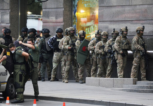 Ukrainian law enforcement officers are seen outside a building where an unidentified man reportedly threatens to blow up a bomb in a bank branch, in Kyiv