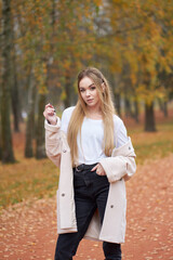 Autumn portrait of young blonde attractive woman wth long hair wearing white shirt, black mom jeans, trendy autumn coat walking in autumn park.