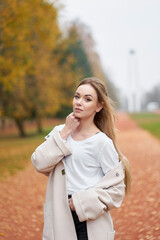 Autumn portrait of beautiful young woman in elegant coat, white basic shirt, black mom jeans in a park on background of trees with orange leaves. Girl walking in park.