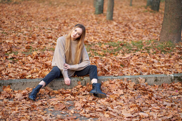 Hipster attractive blonde girl wearing stylish oversize sweater, trendy black mom jeans and youth black leather boots sitting in autumn park.