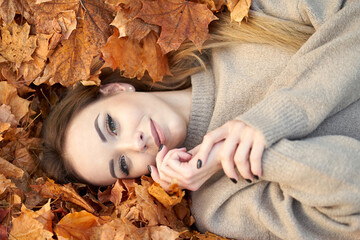 Charming young girl with cute smile liying in the autumn leaves and enjoying it, holding hands near face and smiling. Autumn portrait in the autumn park. Top view.