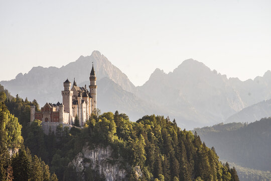 """The fairytale castle """"Neuschwanstein"""" in Bavaria during sunset with mountains in the background"""