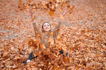 Love autumn. Joyful attractive girl wearing sweater, black jeans and leather black boots sitting and tossing autumn leaves in autumn park.