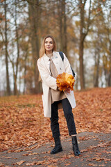 Attractive blonde girl with bouquet of orange maple leaves in the hands wearing fashionable autum coat, black jeans and trendy black leather boots walking in the autumn park.