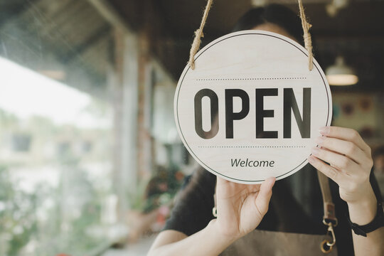 Welcome. Open. barista, waitress woman turning open sign board on glass door in modern cafe coffee shop ready to service, cafe restaurant, retail store, small business owner, food and drink concept