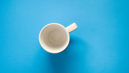 Wall Mural - White coffee cup on blue background