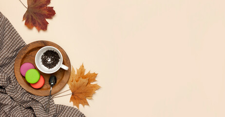 Flat lay autumn composition. White cup with tea leaves, wooden plate, knitted fashion sweater or plaid, pants in a pattern, yellow maple leaves cinnamon orange on beige background top view copy space