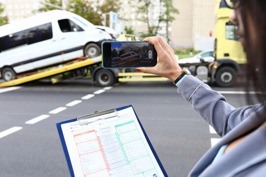 An insurance agent takes photo of crashed car after an accident on smartphone. Car insurance concept