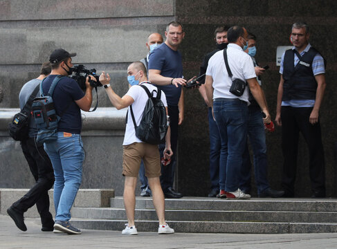 Journalists work outside a building before entering a bank where an unidentified man reportedly threatens to blow up a bomb, in Kyiv