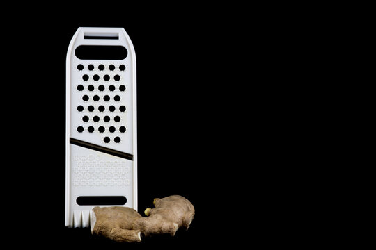 Mandolin Food Slicer and Fresh Ginger on a Black Background