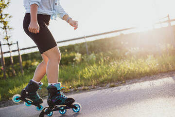 Girl is rollerblading along an asphalt alley in sunny day