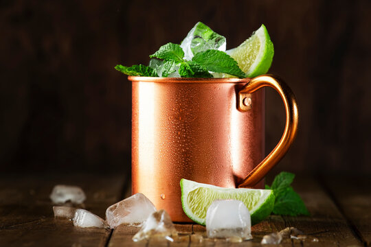 Moscow mule or mint julep cocktail in copper mug with lime, ginger beer, vodka and mint. Wooden table, copper bar tools,  copy space