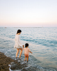 Mom and daughter walking into ocean